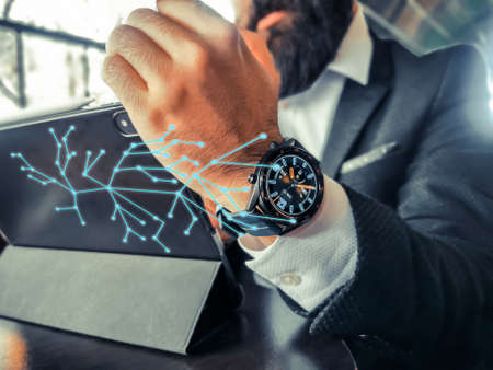 bearded adult rich businessman who has smart watch using his pro tablet and work remotely holographic intel web floating connects his smartphone and smartwatch and tablet