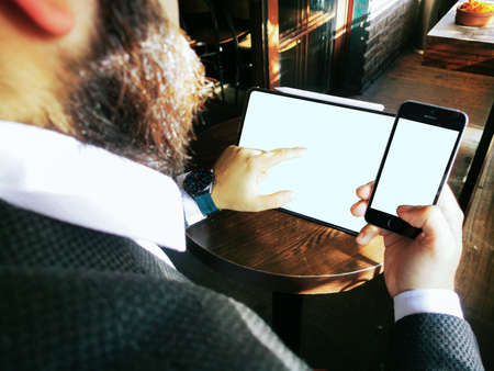 young adult male with beard has a smartphone and touching the pro tablet screen blank 免版税图像