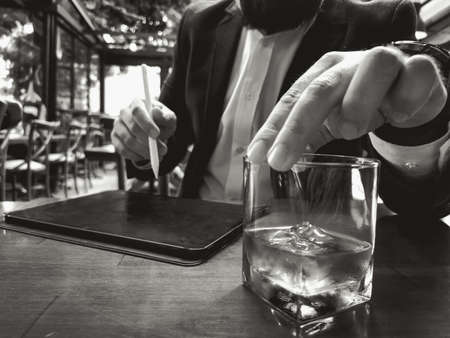 businessman holding whiskey and tablet pencil in a glass with blank new pro tablet screen on the table 免版税图像