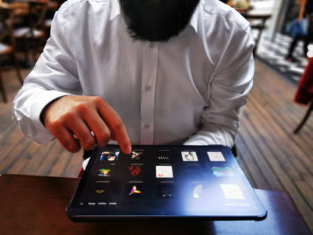young adult businessman touching his pro tablet screen on the table