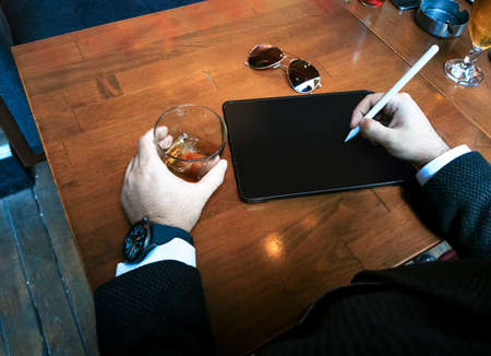 top view businessman with smart watch holding whiskey glass and tablet pencil with his blank screen pro tablet on the table