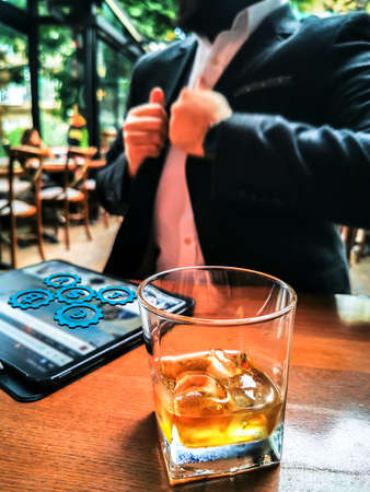 business man with beard using pro tablet and pencil interacting with tablet screen holographic economy icons floating drinking whiskey in the cafe pub 免版税图像