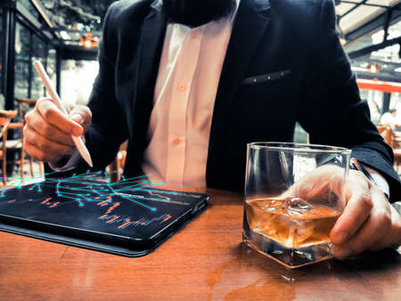 business man with beard using pro tablet and pencil interacting with tablet screen holographic web floating drinking whiskey in the cafe pub