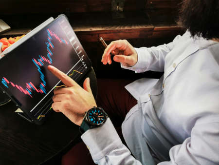 young adult bearded businessman with smart watch smoking cigar and touching his pro tablet screen checking market stock exchange for-ex block chain graphic