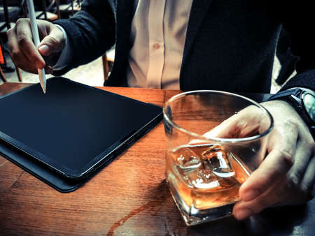 business man with beard who has smart watch using pro tablet and pencil interacting with tablet screen blank screen drinking whiskey in the cafe pub