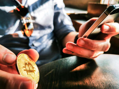 young adult male with sunglasses and watch using his smartphone and flipping gold bitcoin on the table
