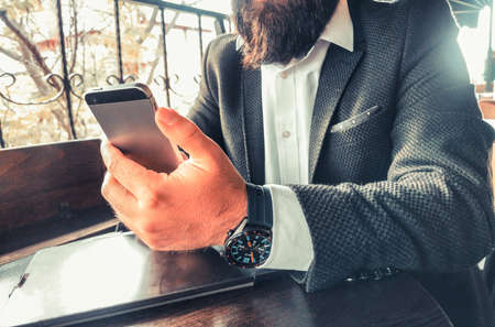 hipster adult rich businessman with beard and smartwatch using his pro tablet and his smartphone