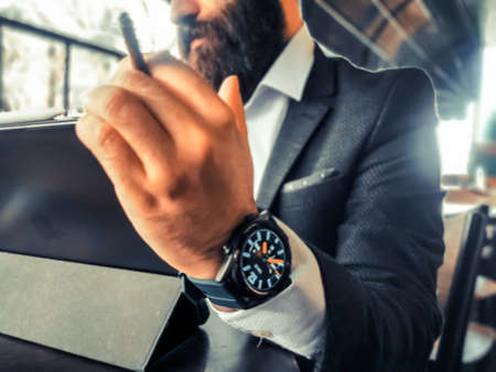 bearded adult rich businessman smoking who has smart watch using his pro tablet and work remotely
