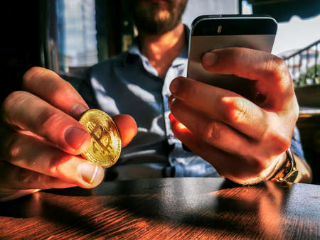 young adult male with sunglasses and watch using his smartphone and flipping bitcoin on the bar table