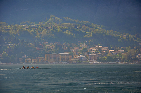 View of Lake Como on a cloudy day with rowers in the foreground in Bellagio, a charming tourist village between the lake and the mountains of the Alps. Located in the Lombardy region, northern Italy