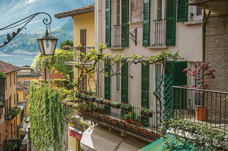shutter: Como, Italy - May 06, 2013. View of Como Lake, balconies with open blinds and bindweed in Bellagio, a charming village between the lake and the mountains of Alps. Lombardy region, northern Italy