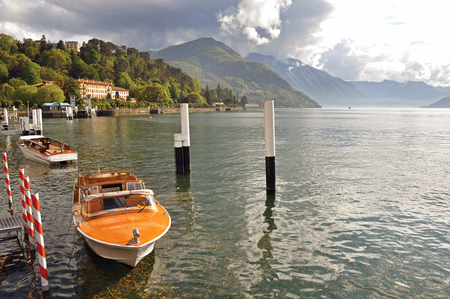Como, Italy - May 06, 2013. View of Lake Como in a sunny day with motorboat and harbor in Bellagio, a charming village between the lake and the mountains of Alps. Lombardy region, northern Italy