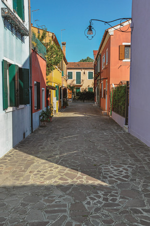 venice: Overview of colorful terraced houses, lamp and buses in an alley on sunny day in Burano, a gracious little town full of canals, near Venice. Located in the Veneto region, northern Italy