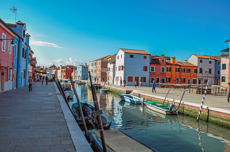 Burano, Italy - May 08, 2013. Colorful buildings, people and boats in front of the canal at Burano, a gracious little town full of canals, near Venice. Located in the Veneto region, northern Italy Editorial