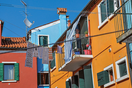 shutter: View of colorful terraced houses, balcony and clothes hanging in an alley on sunny day in Burano, a gracious little town full of canals, near Venice. Located in the Veneto region, northern Italy Stock Photo