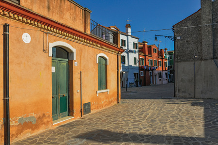 Overview of colorful terraced houses in an alley, in the sunset at the city center of Venice, the historic and amazing marine city. Located in the Veneto region, northern Italy