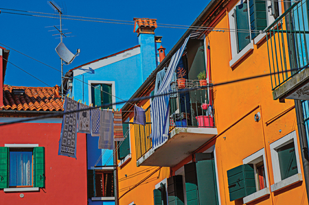 venice: View of colorful terraced houses, balcony and clothes hanging in an alley on sunny day in Burano, a gracious little town full of canals, near Venice. Veneto region, northern Italy. Retouched photo Stock Photo