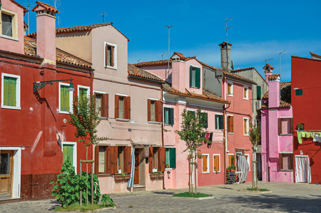 shutter: Overview of colorful terraced houses on sunny day in Burano, a gracious little town full of canals, near Venice. Located in the Veneto region, northern Italy Stock Photo