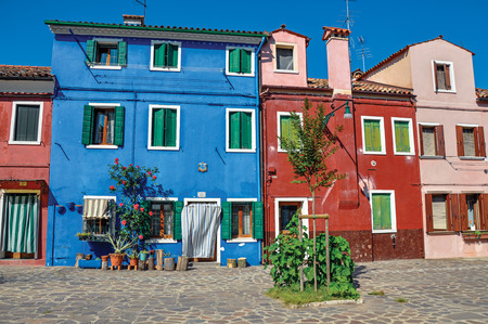 venice: Burano, Italy - May 08, 2013. Overview of colorful terraced houses on sunny day in Burano, a gracious little town full of canals, near Venice. Located in the Veneto region, northern Italy