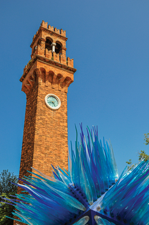 View of clock tower made of bricks and a star shape glass sculpture at Murano, a small and pleasant town on top of islands near Venice. Located in the Veneto region, northern Italy