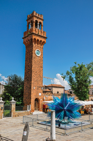 Murano, Italy - May 08, 2013. View of clock tower made of bricks and a star shaped glass sculpture at Murano, a little town on top of islands near Venice. Located in the Veneto region, northern Italy