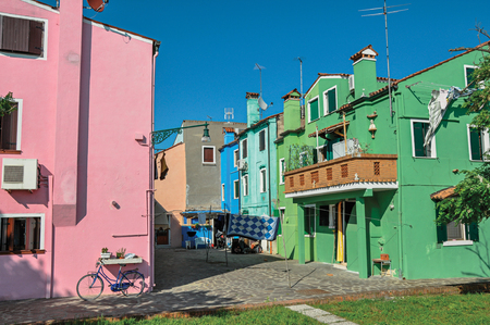 shutter: Overview of colorful terraced houses, balcony and clothes hanging in an alley on sunny day in Burano, a gracious little town full of canals, near Venice. Located in the Veneto region, northern Italy