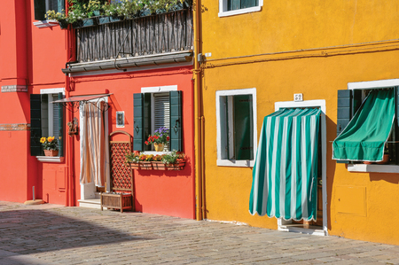 venice: Burano, Italy - May 08, 2013. Close-up of colorful houses and doors with cloth on a sunny day in Burano, a gracious little town full of canals, near Venice. Located in Veneto region, northern Italy Stock Photo