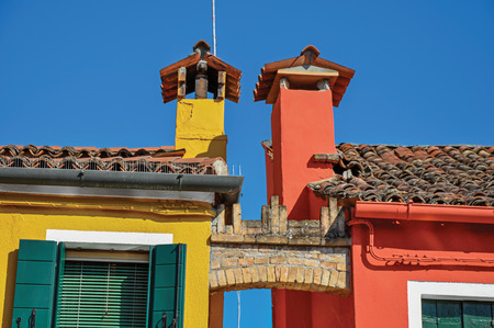 Close-up of chimneys and arch between colorful terraced houses on sunny day in Burano, a gracious little town full of canals, near Venice. Located in the Veneto region, northern Italy