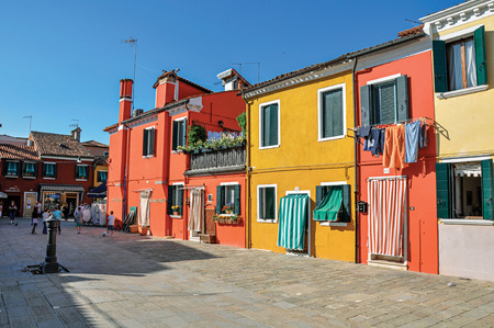 shutter: Burano, Italy - May 08, 2013. Close-up of colorful houses and doors with cloth on a sunny day in Burano, a gracious little town full of canals, near Venice. Located in Veneto region, northern Italy Editorial