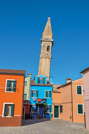 venice: Burano, Italy - May 08, 2013. Overview of colorful buildings and leaning bell tower in a sunny sunny day at Burano, a gracious little town full of canals, near Venice. Veneto region, northern Italy