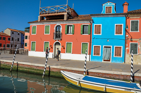 venice: Burano, Italy - May 08, 2013. Colorful buildings, people and boats in front of the canal at Burano, a gracious little town full of canals, near Venice. Located in the Veneto region, northern Italy Editorial