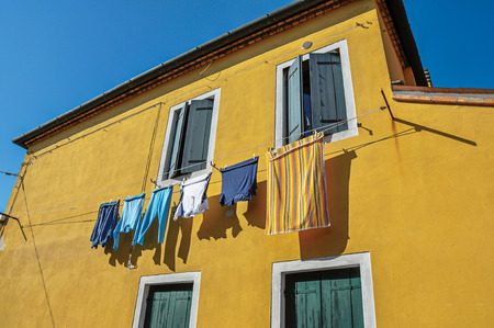 shutter: Close-up of windows on colorful walls and clothes hanging on sunny day in Burano, a gracious little town full of canals, near Venice. Located in the Veneto region, northern Italy