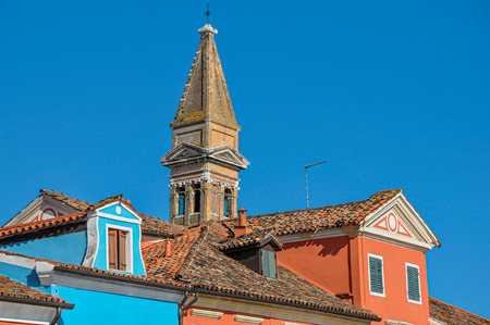 Close-up of colorful buildings, bell tower and rooftops in a sunny sunny day at Burano, a gracious little town full of canals, near Venice. Located in the Veneto region, northern Italy