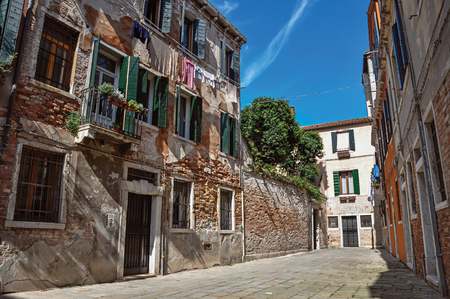 Overview of old brick buildings in an alley with sunny blue sky in the city center of Venice, the historic and amazing marine city. Located in Veneto region, northern Italy