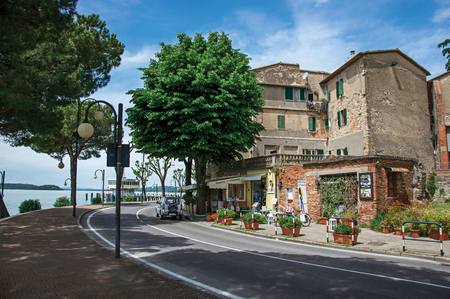 Passignano sul Trasimeno, Italy - May 15, 2013. View of the hamlet and its promenade on the shores of Lake Trasimeno, a quiet and picturesque lake near Perugia. Located in Umbria region, central Italy