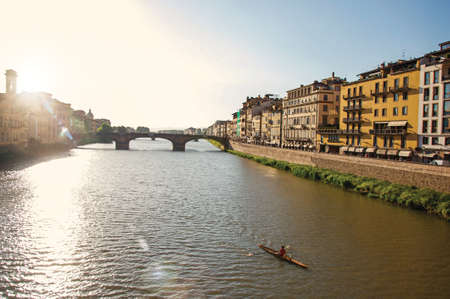 Overview of rower on the river Arno, bridge and buildings at sunset. In the city of Florence, the famous and amazing capital of the Italian Renaissance. Located in the Tuscany region. Retouched photo