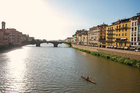 Overview of rower on the river Arno, bridge and buildings at sunset. In the city of Florence, the famous and amazing capital of the Italian Renaissance. Located in the Tuscany region Stock Photo