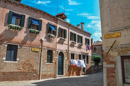 venice: Overview of ancient houses and clothes hanging in an alley on sunny day. At the city center of Venice, the historic and amazing marine city. Located in Veneto region, northern Italy