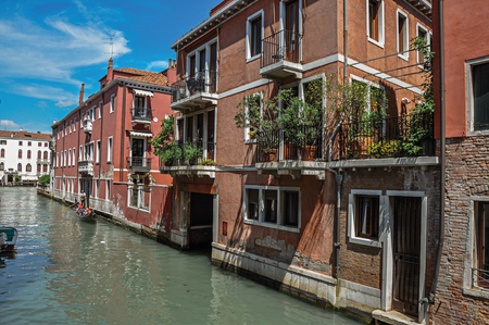 shutter: View of buildings in front of the canal with gondola in the background, at the city center of Venice, the historic and amazing marine city. Veneto region, northern Italy Stock Photo
