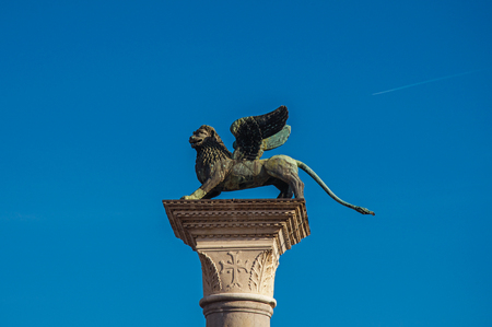 Close-up of column with the winged lion, symbol of Venice, and sunny blue sky in Piazza San Marco. At the city of Venice, the historic and amazing marine city. Located in Veneto region, northern Italy