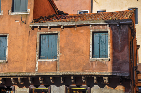 shutter: Close-up of windows in medieval house with green blinds closed. At the city center of Venice, the historic and amazing marine city. Located in Veneto region, northern Italy Stock Photo