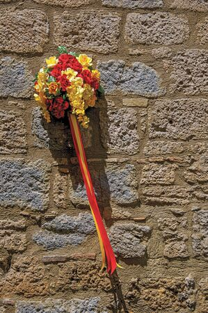Close-up of a bouquet of colorful flowers hanging from a stone wall in the lane of Orvieto, a pleasant and well preserved medieval city. Located in Umbria, central Italy