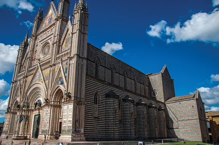 Orvieto, Italy - May 17, 2013. Panoramic view of the Orvieto Cathedral (Duomo) with people in Orvieto, a pleasant and well preserved medieval town. Located in Umbria, central Italy