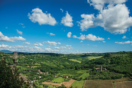 edad de piedra: Overview of green hills, vineyards, forests and towered stronghold in a sunny day. In front of the Orvieto town, an ancient, pleasant and well preserved medieval town. Located in Umbria, central Italy