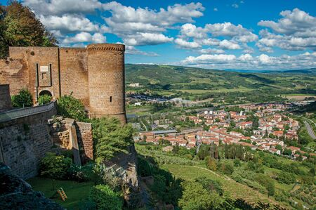 Overzicht van stenen toren, groene heuvels, wijngaarden en daken van de stad in de buurt van de weg. Vanuit het centrum van Orvieto, een oud, aangenaam en goed bewaard gebleven middeleeuws stadje. Gelegen in Umbrië, Midden-Italië Stockfoto