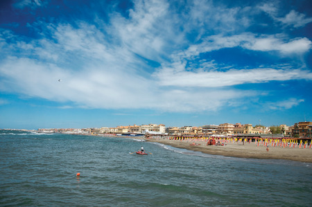 bather: Overview of the beach and town of Ostia between the Mediterranean sea and sunny sky. The town is a seaside resort and ancient port of Rome. Located in the Lazio region Stock Photo