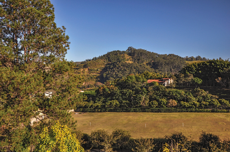 Overview of hills with woods and house in the sunrise, near Monte Alegre do Sul. In the countryside of S?o Paulo State, the region rich in agricultural and livestock products, southwestern Brazil