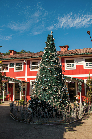 painted wood: Penedo, Brazil - January 18, 2015. View of Christmas tree and wooden house on sunny day in Penedo, a tourist town founded by Finns who still has strong influence of this culture. Rio de Janeiro State Editorial