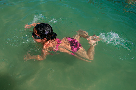 Overview of child swimming in the sea on sunny day in Pelado Island, a tropical beach near Paraty, an amazing and historic town totally preserved in Rio de Janeiro State, southwestern Brazil Imagens