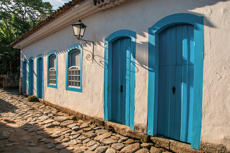 street lamp: Overview of cobblestone street with old houses at the sunset in Paraty, an amazing and historic town totally preserved in the coast of Rio de Janeiro State, southwestern Brazil Stock Photo